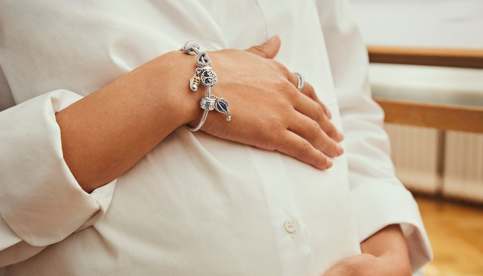 Sterling silver bracelet styled with charms celebrating baby's arrival