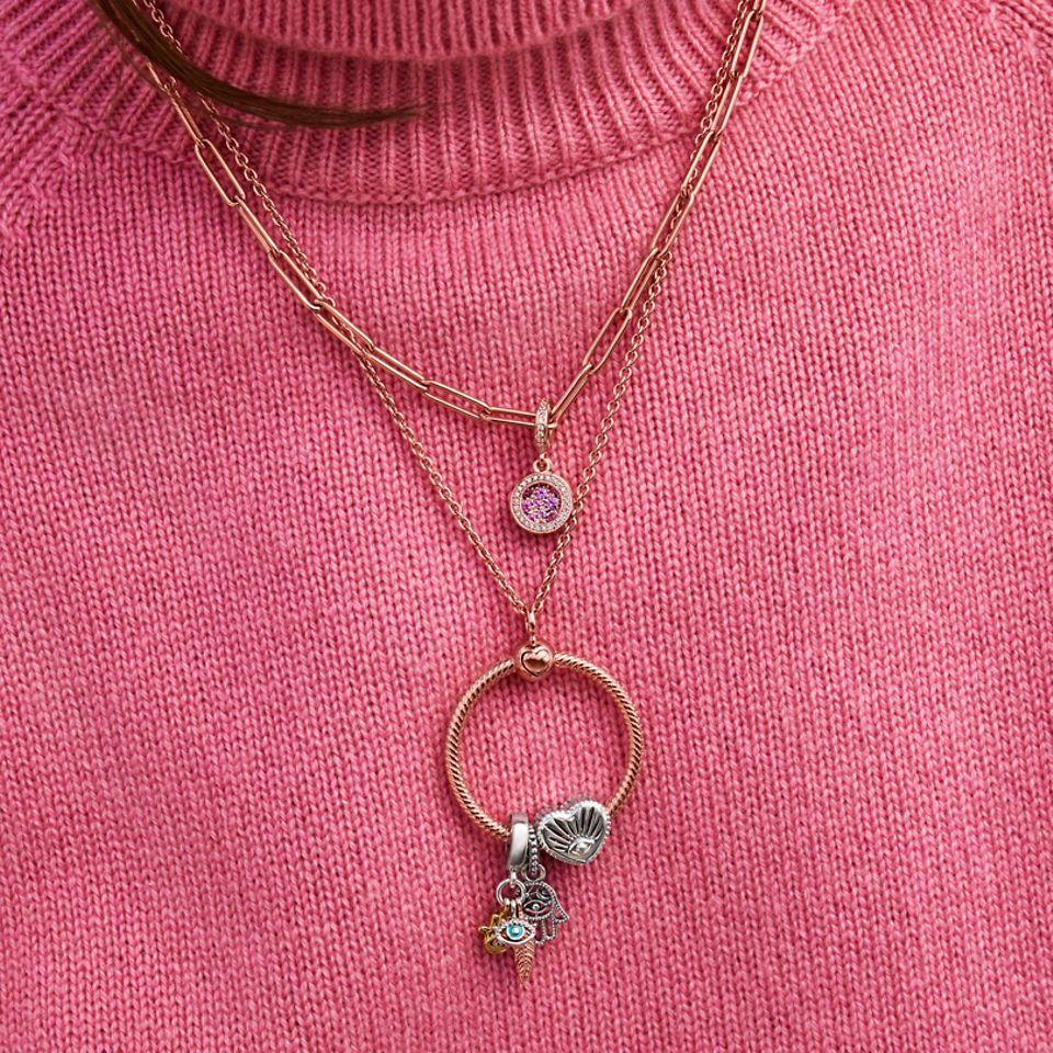 En model, der bærer to halskæder i Pandora Rose, begge med O Pendant og stylet med symbolske charms