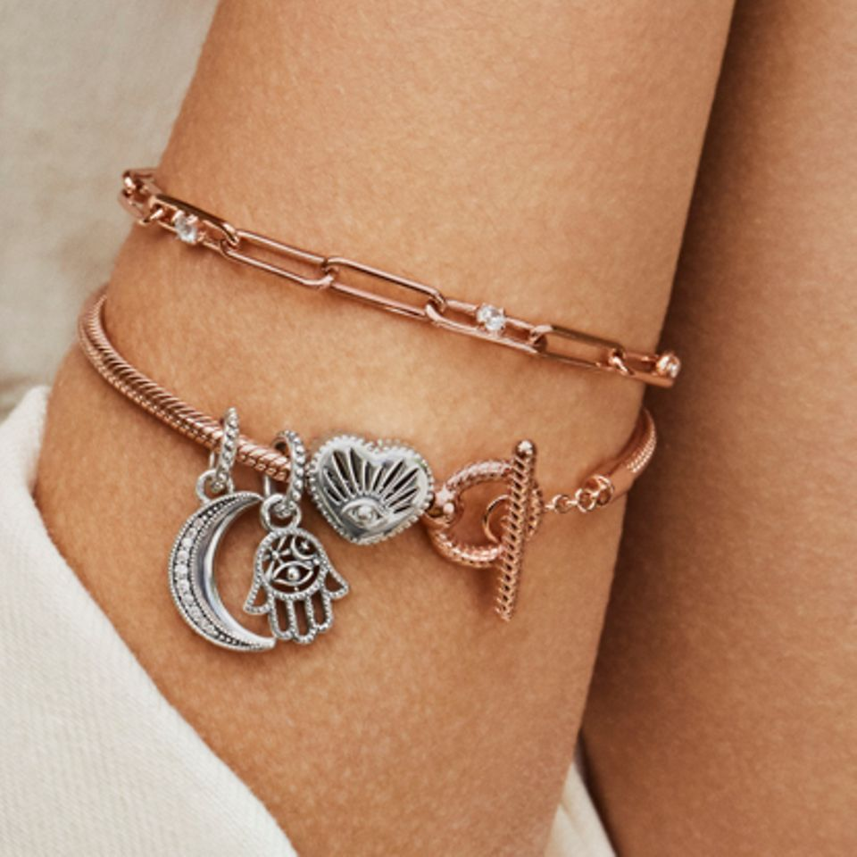 Model showing her arm and wearing two Pandora Rose bracelets including charms from the Pandora Passions collection