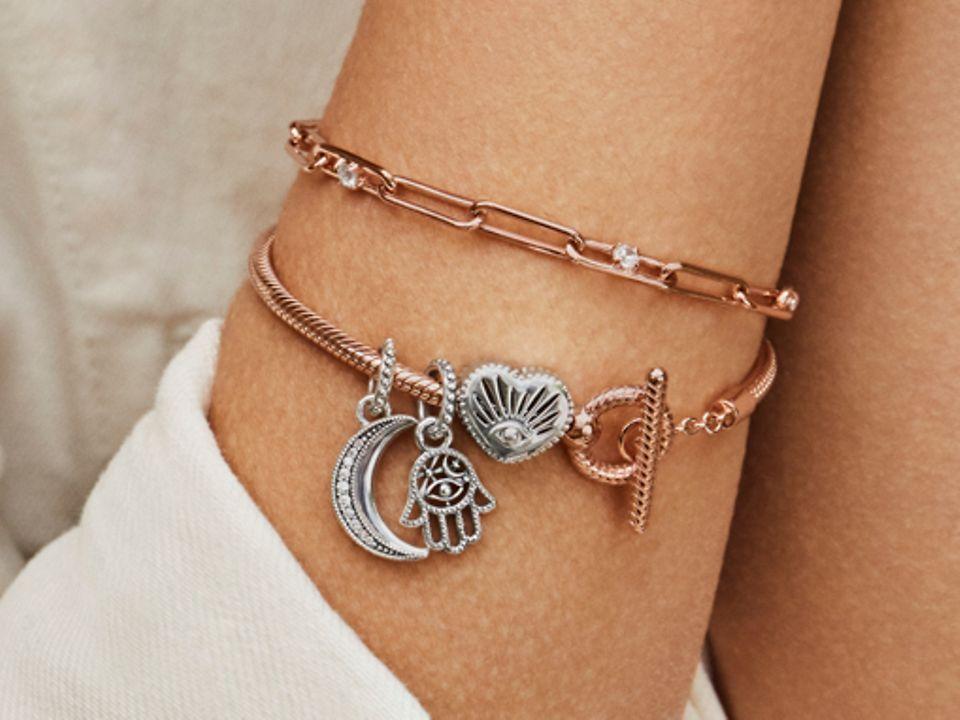 露出的模特手腕上戴着两条串着象征物系列串饰的Pandora Rose手链