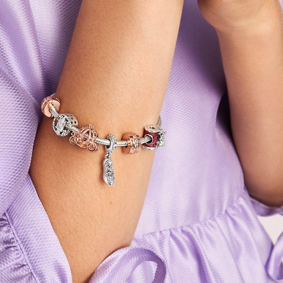 Modella che indossa i charm ispirati alla Cenerentola Disney della collezione Disney x Pandora.