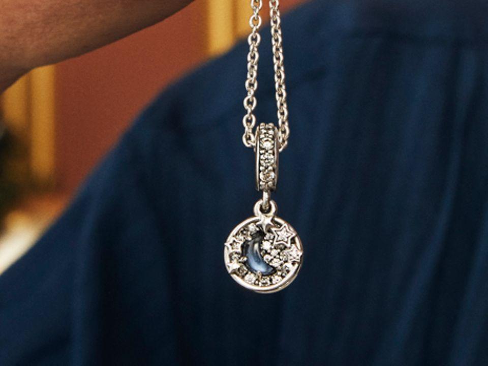 Pandoraネックレスとリングを持ち、チャームブレスレットとネックレスをまとったモデル。