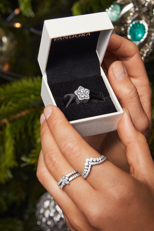 Anelli Pandora Timeless indossati da una modella e charm scintillante con fiocco di neve in una scatola.