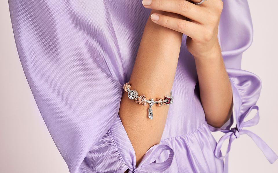 En model, der bærer Disneys Askepot charms fra Disney x Pandora Collection.