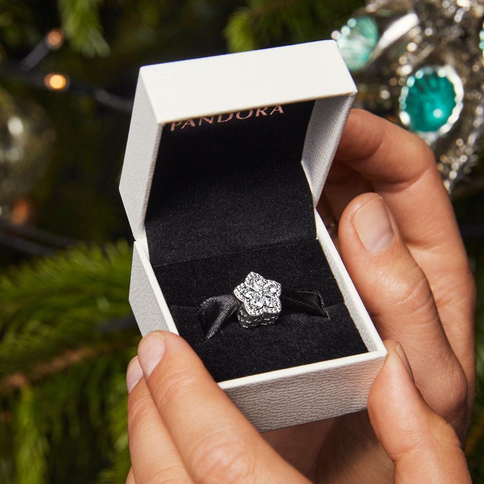 Modelka nosząca pierścionki Pandora Timeless i charms z lśniącym płatkiem śniegu w pudełku.