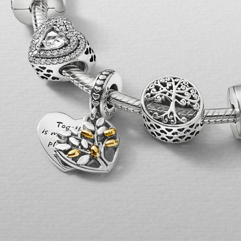 Pandora People berlocker stylade på ett armband och halsband från Pandora Moments.