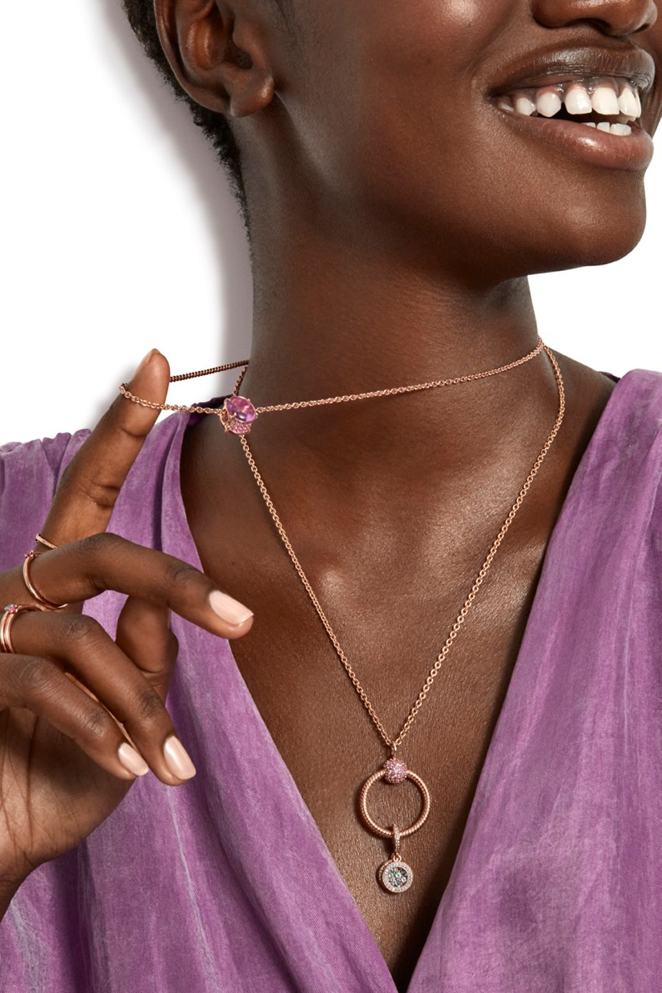 Model wearing Pandora Colours rings and charms on a necklace and pendant.