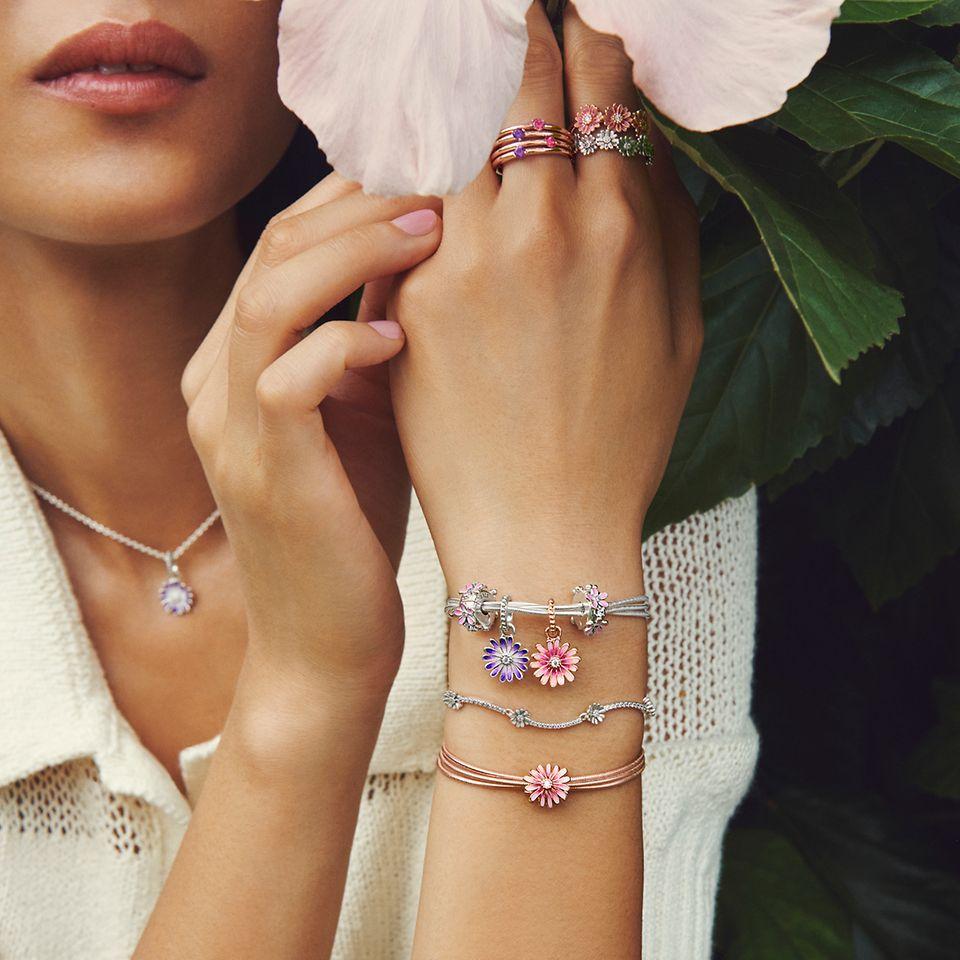 Model met bloem, die Pandora Garden-madeliefjesarmbanden, -ringen en -bedels draagt.