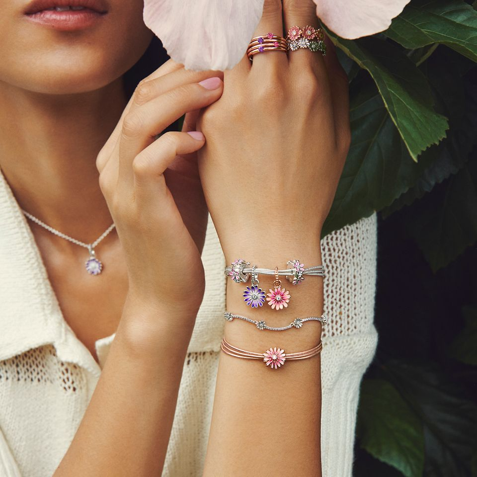 Model holding flower, wearing Pandora Garden daisy bracelets, rings and charms.