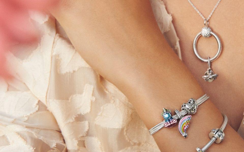 Model draag Pandora Moments-armband, -halsketting en -bedels.
