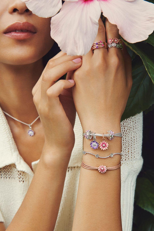 Model med blomst i hånden, der bærer margueritarmbånd, -ringe og -charms fra Pandora Garden.