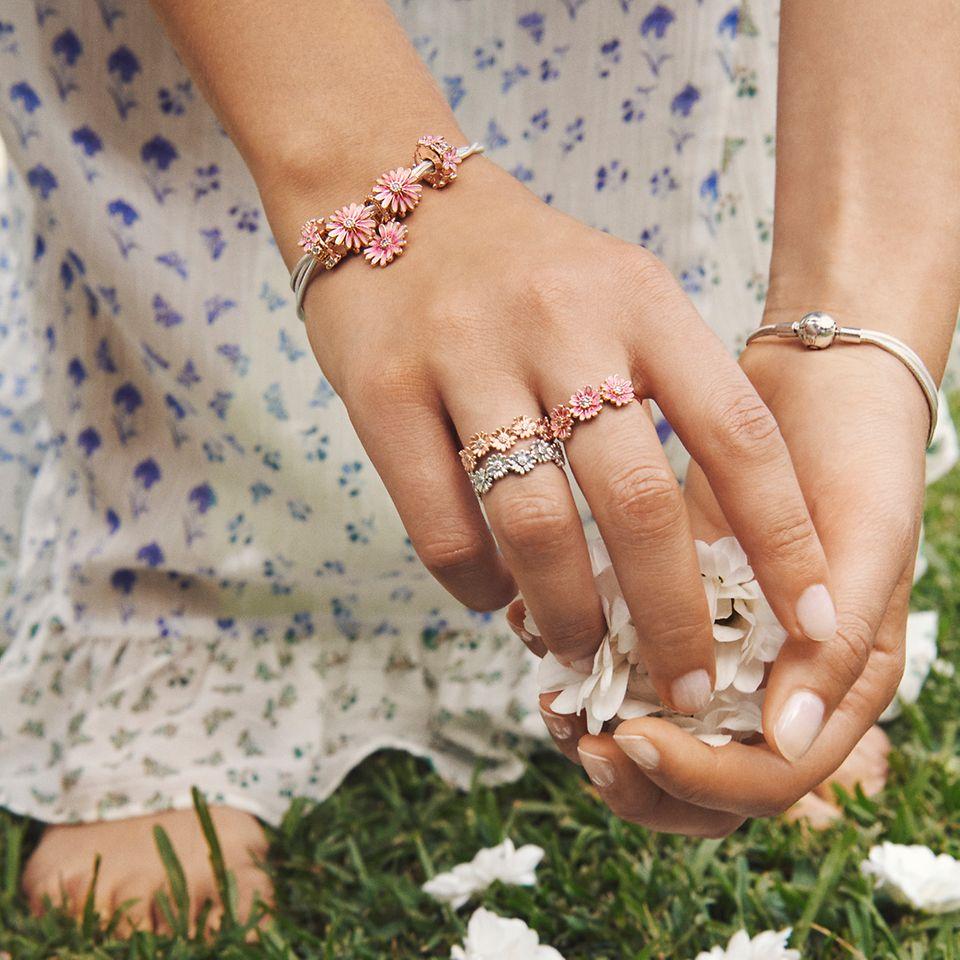 採摘雛菊的模特兒佩戴 Pandora Garden 系列雛菊戒指、手鏈和串飾。