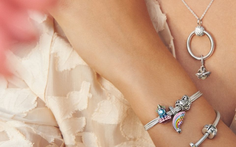 Modelka nosząca bransoletki, naszyjnik i charmsy Pandora Moments.
