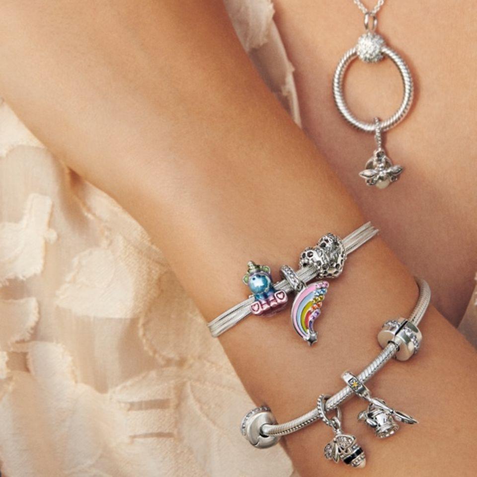 Modella che indossa un bracciale, una collana e charm Pandora Moments.