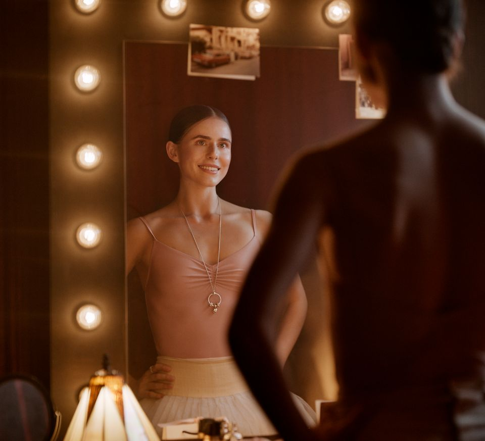 A ballerina proudly looking at her reflection while wearing a Pandora O Pendant.
