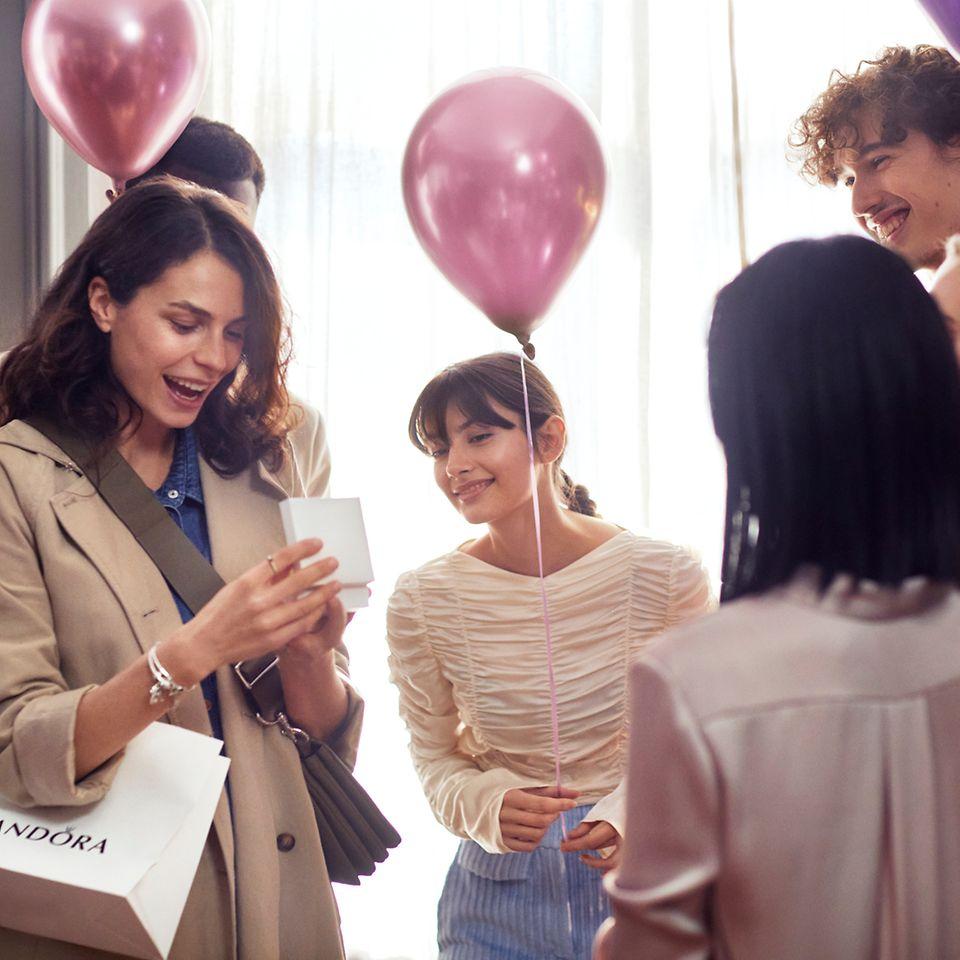 A surprised woman receiving Pandora birthday jewellery.