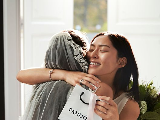 A bride receiving Pandora bridal jewellery as a gift from a friend.