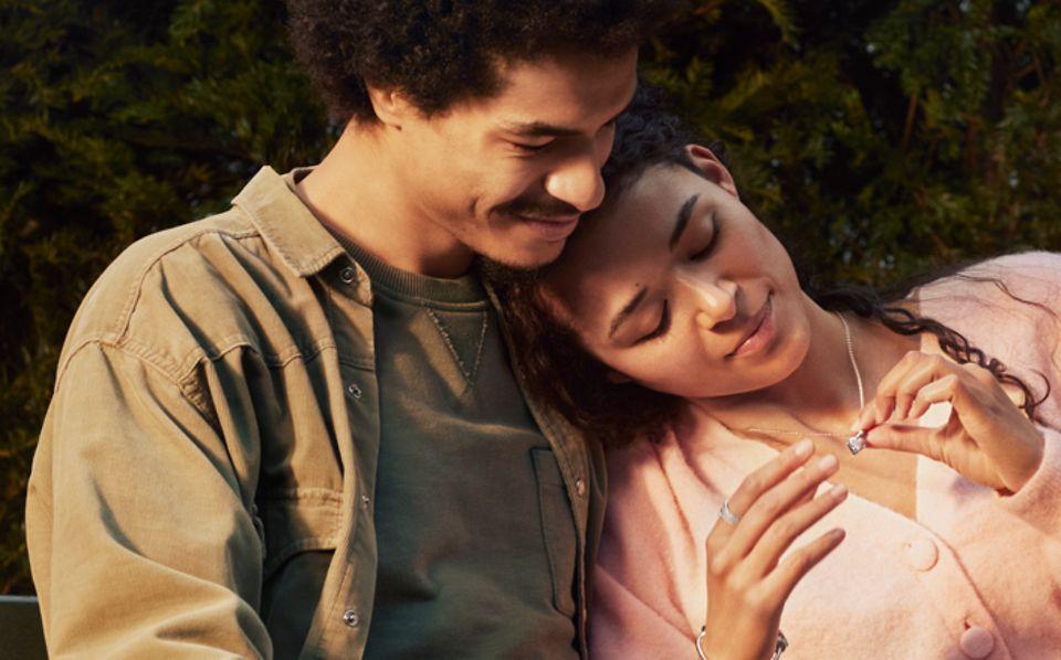 Couple sur un banc, la femme reçoit un bijou Pandora pour son anniversaire.