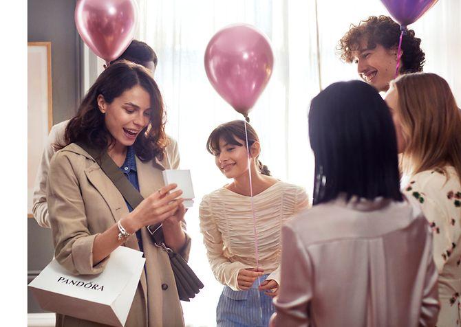 Una donna sorpresa che riceve un gioiello Pandora per il suo compleanno.
