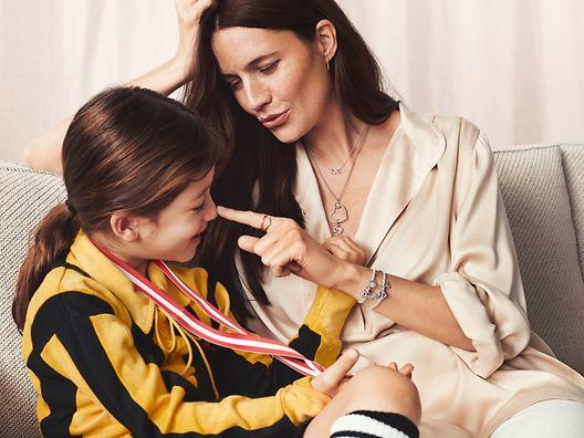 與女兒同坐的母親,佩戴 Pandora O 形吊墜和串飾手鏈。