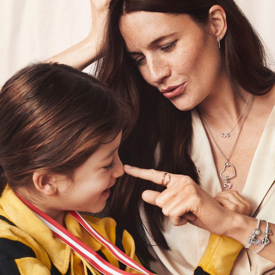 Mutter und Tochter sitzen zusammen, die Mutter trägt den Pandora O Pendant Kettenanhänger und Charm-Armbänder.