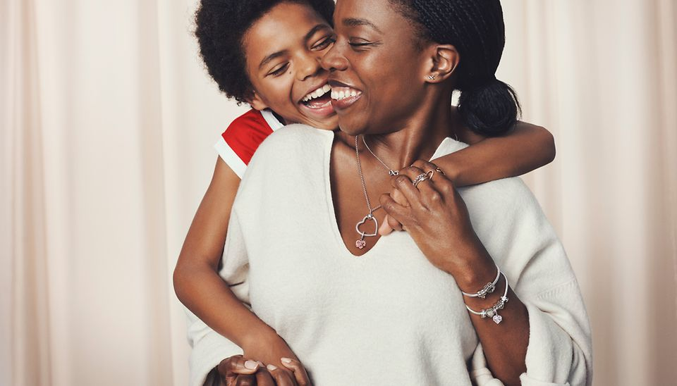 Mother embracing child while wearing Pandora Heart O Pendant and bracelets.
