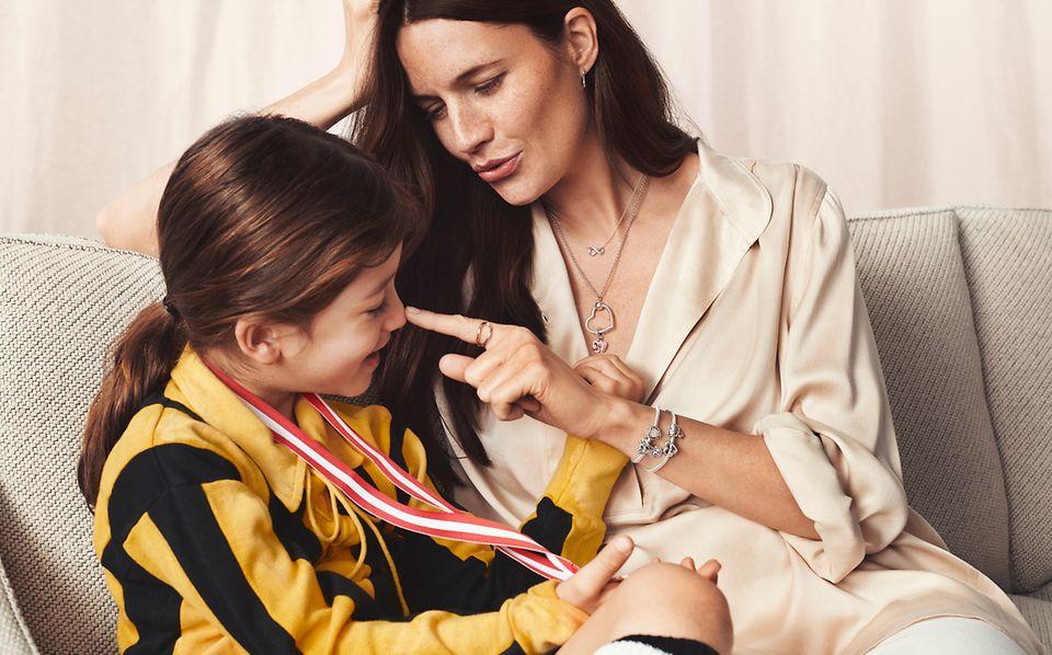 母亲佩戴 Pandora 字母 O 吊坠及串饰手链与女儿坐在一起。