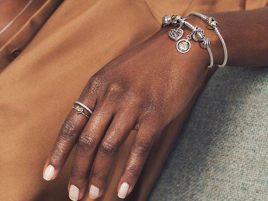 Model trägt Pandora Moments Bicolor-Ringe, Armband und Charms.