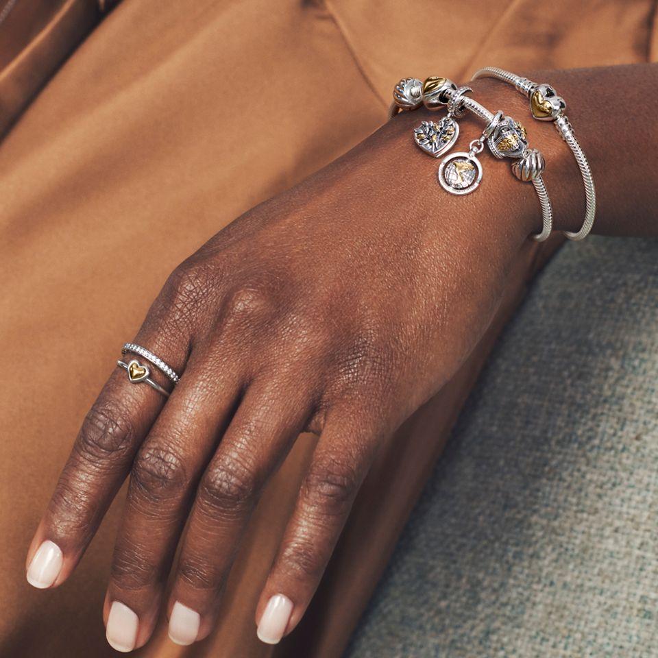 Modella che indossa bracciale, charm e anelli bicolore Pandora Moments.