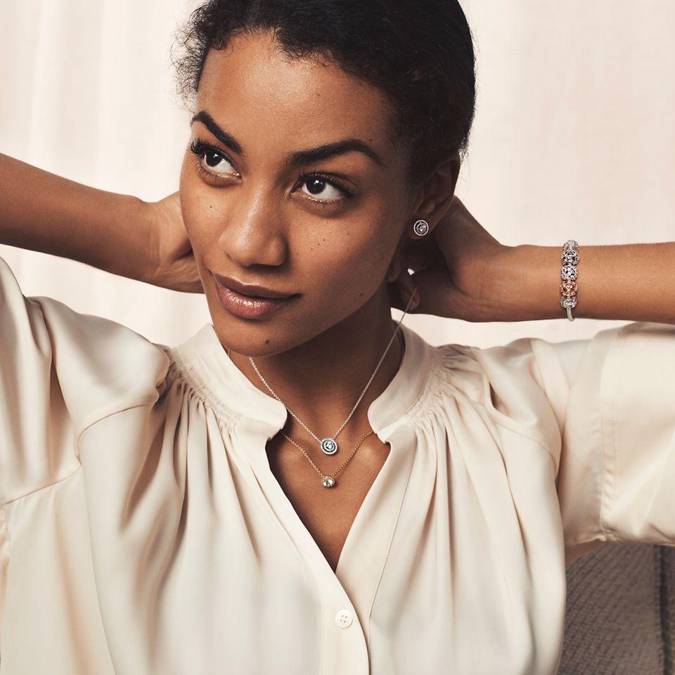 Model met Pandora Timeless halskettingen, armband en oorbellen.