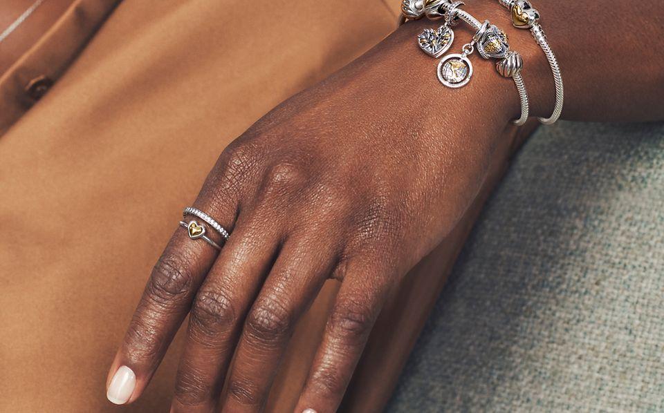 Modelka nosząca dwutonowe pierścionki bransoletki i charmsy Pandora Moments.