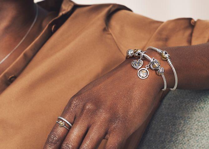 Modelo llevando anillos, pulsera y charms en dos tonos de Pandora Moments.