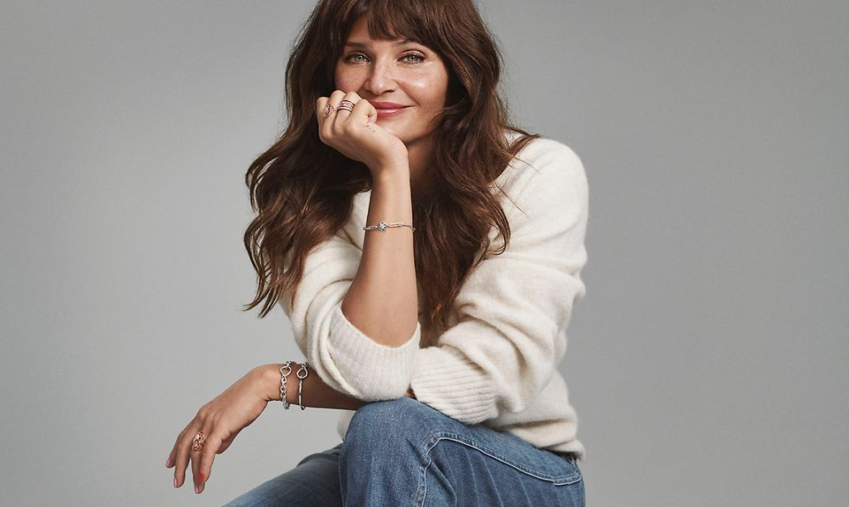 Helena Christensen, zittend, met Pandora-armbanden en ringen.