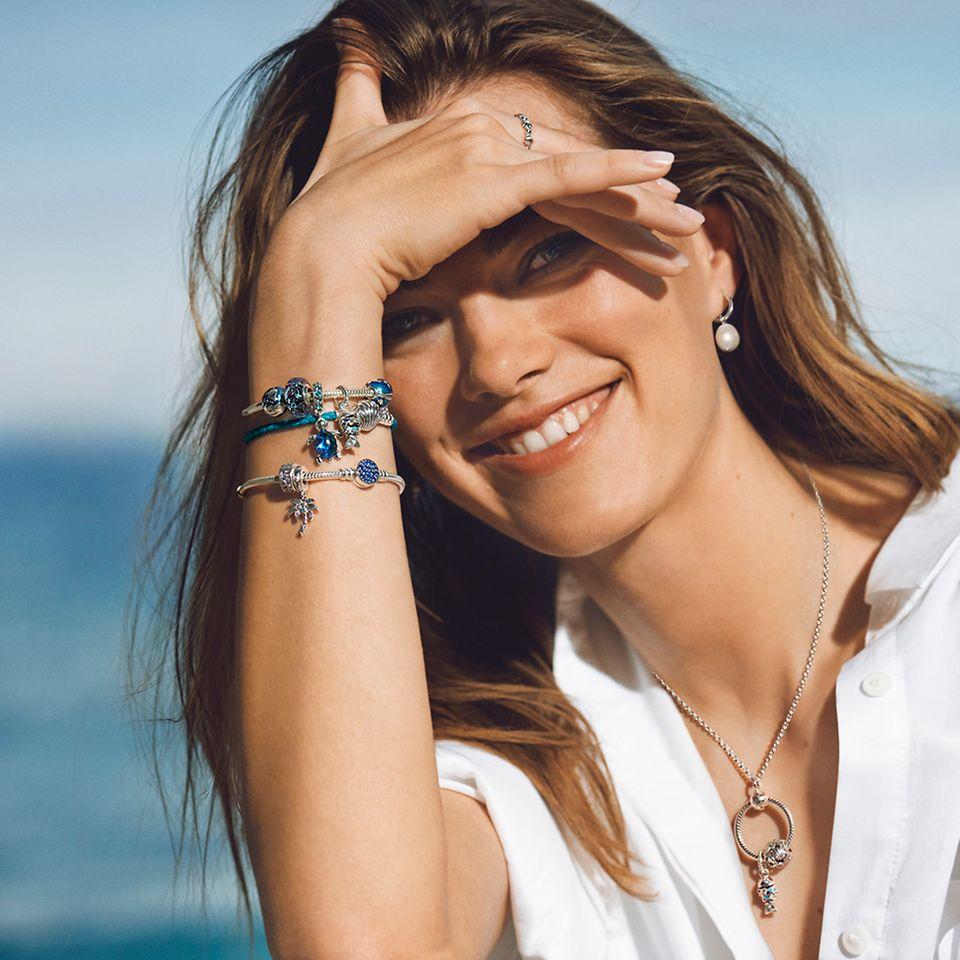 Lächelnde Frau, trägt die Pandora Blue Ocean Armbänder und den Pandora O Pendant