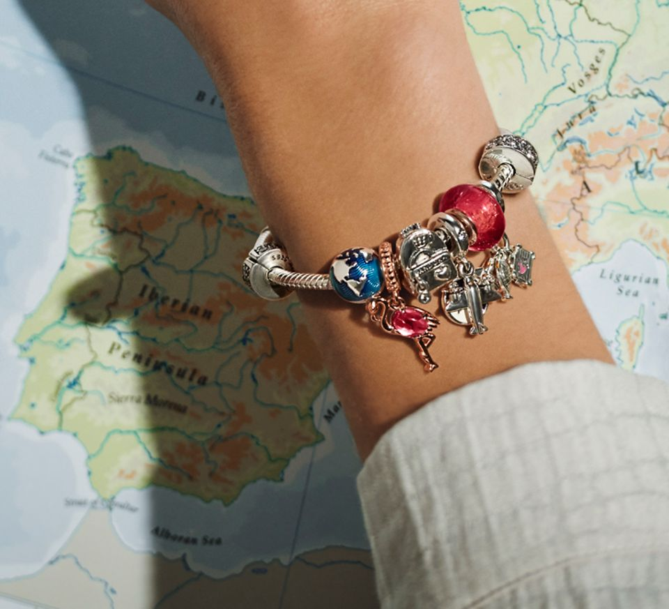 Hand with a Pandora Moments bracelet with travel & national icons charms & map