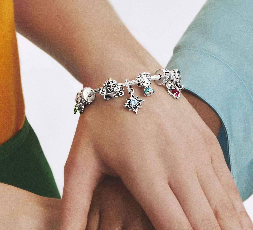 Two models wearing colourful charms bracelets from Disney x Pandora