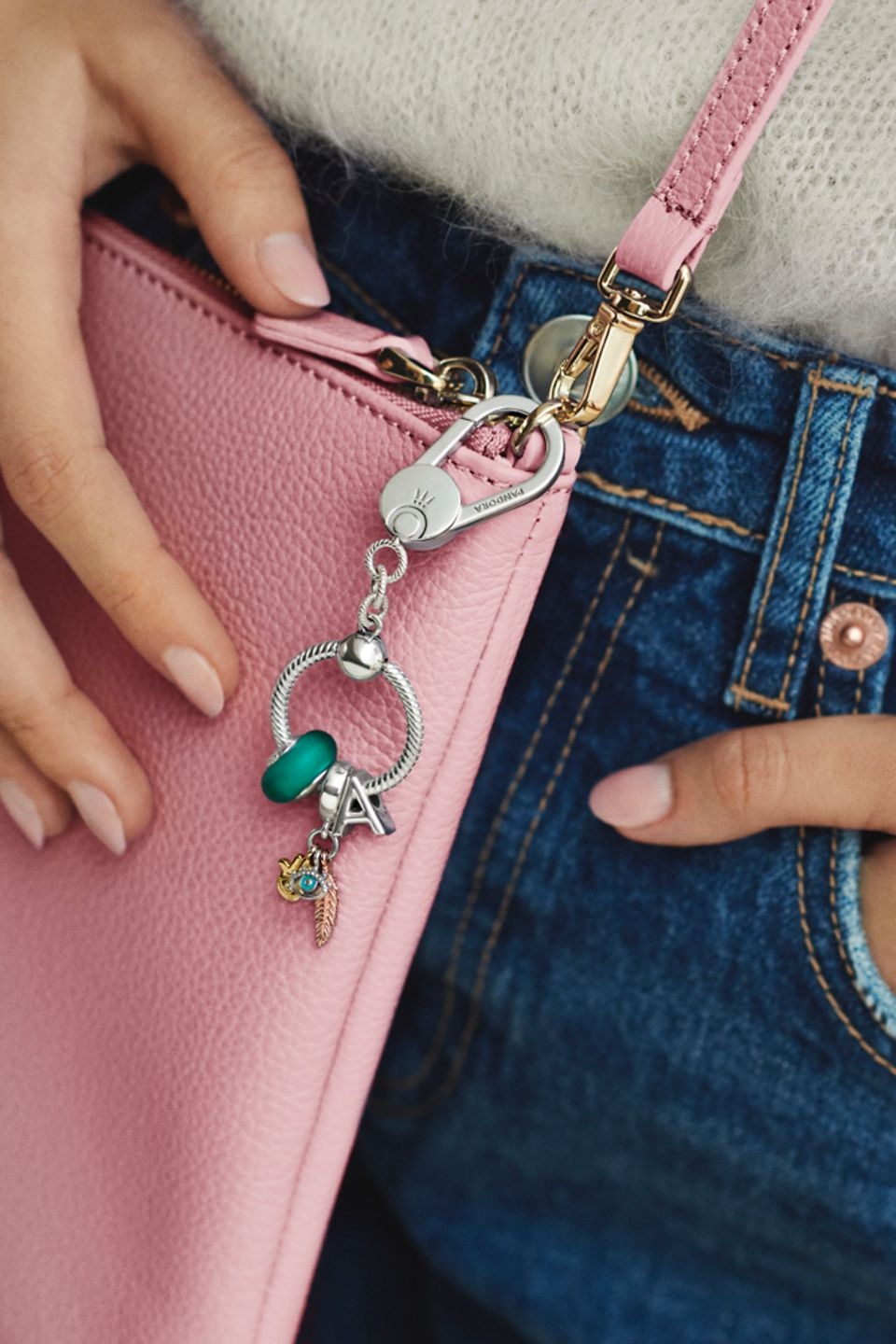 Woman holding a bag accessorised with Pandora Moments charms
