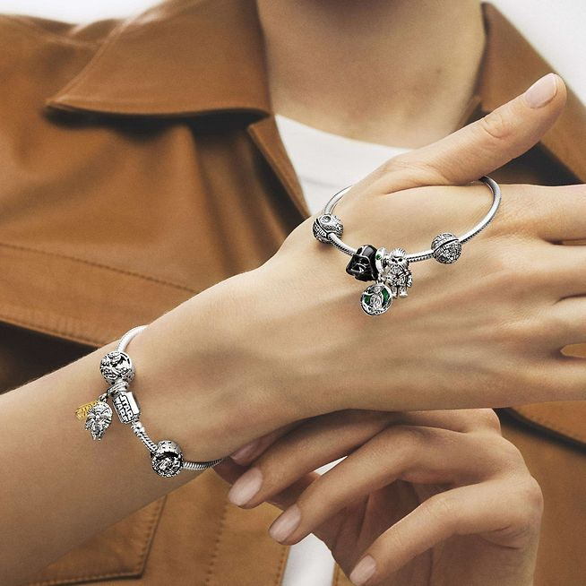 Woman wearing sterling silver bracelet with colourful charms from Star Wars x Pandora