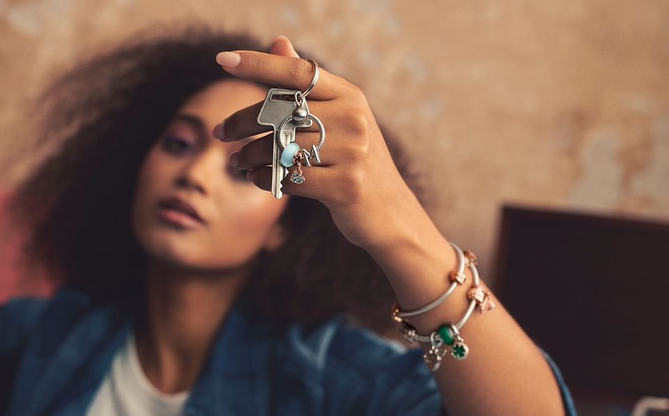 Woman holding Pandora Moments key ring with charms and wearing colourful charm bracelet