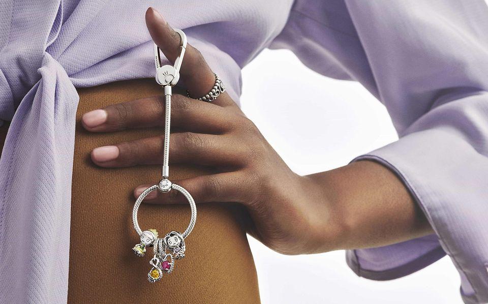 Modelo sosteniendo un colgante de bolso en plata de primera ley embellecido con charms de Disney x Pandora