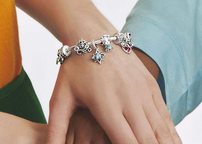 Zwei Models tragen farbenfrohe Charm-Armbänder von Disney x Pandora