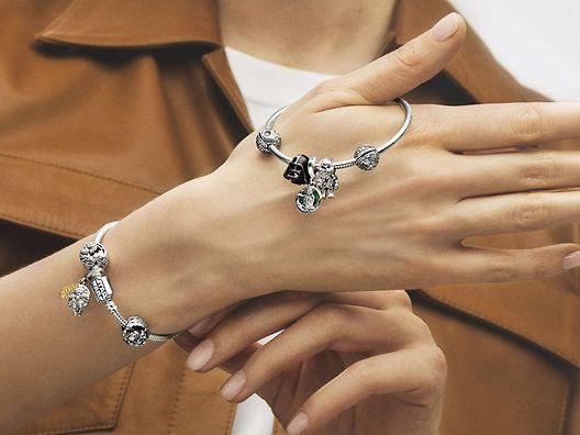 Donna che indossa un bracciale in argento sterling 925 con charm colorati della collezione Star Wars x Pandora