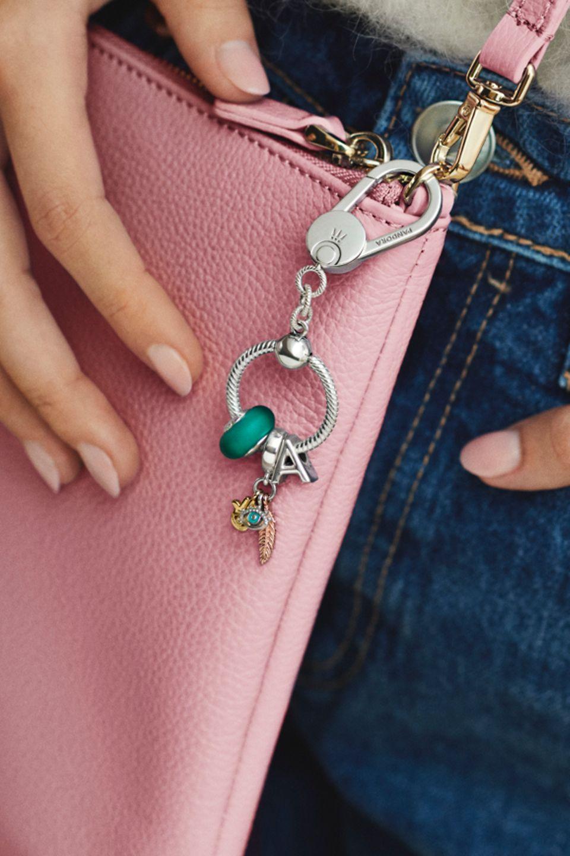 Donna con una borsetta decorata da charm Pandora Moments