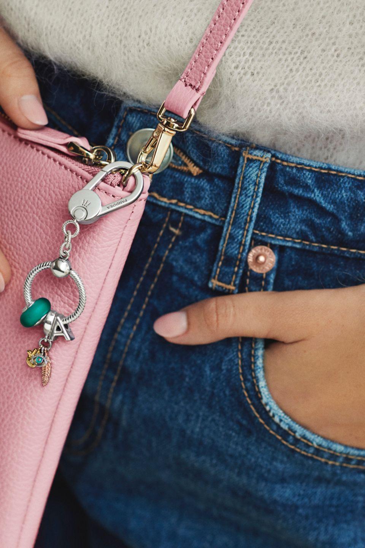 女子手持飾以 Pandora Moments 串飾的手袋