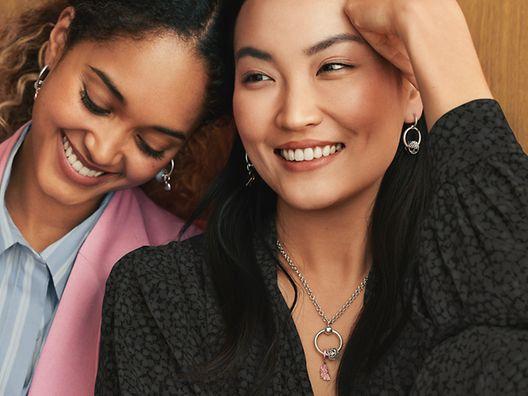 Two Women wearing Pandora Moments hoop earrings and Pandora O Pendant