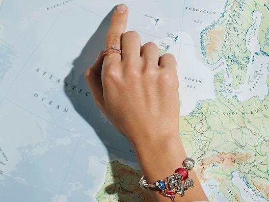 旅とナショナルアイコンがテーマのチャームをつけたPandora Momentsブレスレットをまとった手