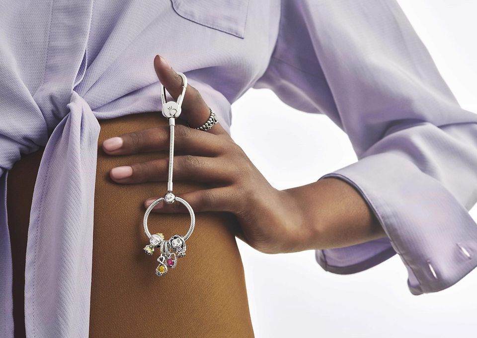 Model holding a sterling silver bag carrier with charms from Disney x Pandora