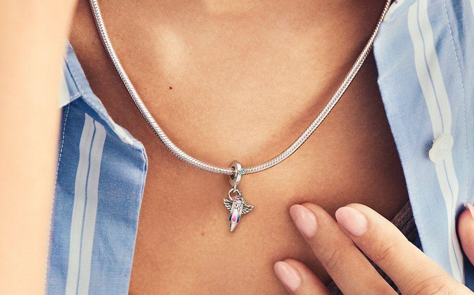 Une femme porte un collier à pendentif en argent et le charm pour l'UNICEF