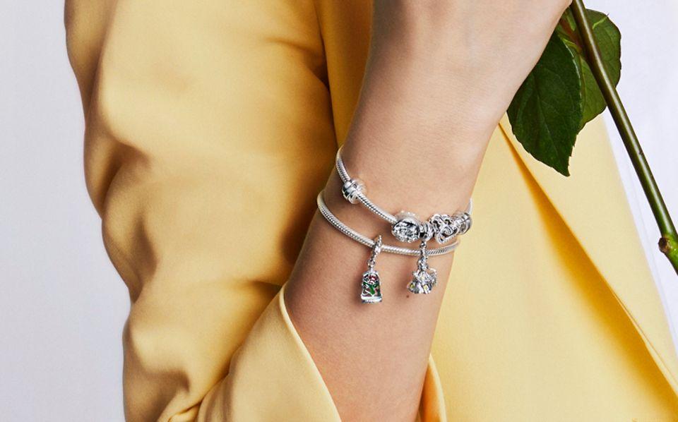 Femme portant une bague et un bracelet La Belle et La Bête avec des charms