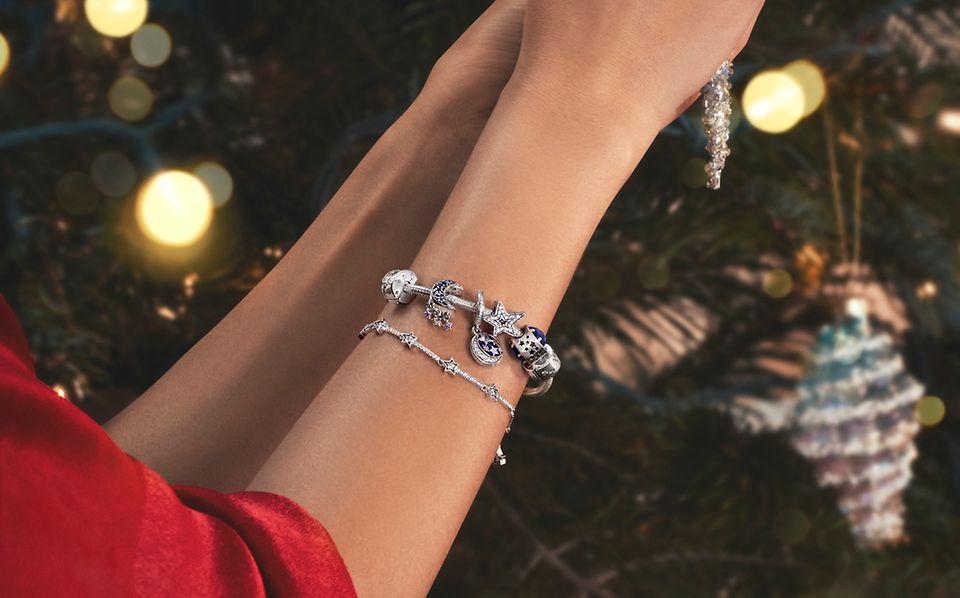Femme décorant un arbre et portant une bague et un bracelet Pandora Moments agrémenté de charms.